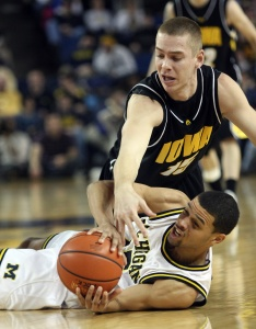 Michigan guard David Merritt, bottom, contests for the ball with Iowa guard Devan Bawinkel, top, in the second half of an NCAA college basketball game, Sunday, Jan. 11, 2009, in Ann Arbor, Mich. Michigan won 64-49. (AP Photo/Tony Ding)