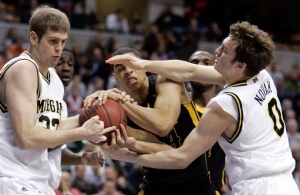 Iowa forward Aaron Fuller, center, battles to maintain control of the ball against Michigan forward Zack Gibson, left, and guard Zack Novak during the first half of an NCAA college basketball game at the Big Ten men's tournament Thursday, March 12, 2009 in Indianapolis. (AP Photo/Michael Conroy)